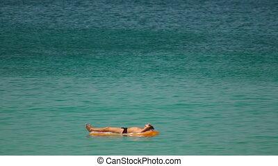 Sunbathes in ocean