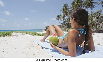 Sunbathing bikini woman relaxing lying down tanning under the tropical sun on Caribbean beach travel holiday, holding a green coconut fruit to drink refreshing healthy fresh fruit water.