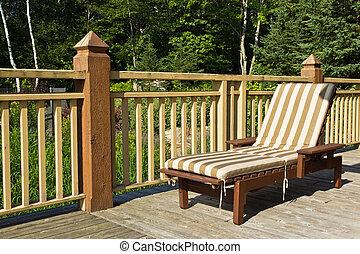 Sunbathing chair on a wooden deck