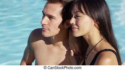 Sunbathing couple sit beside swimming pool