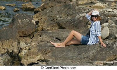 Sunbathing on Rocky Coast - Young attractive woman...