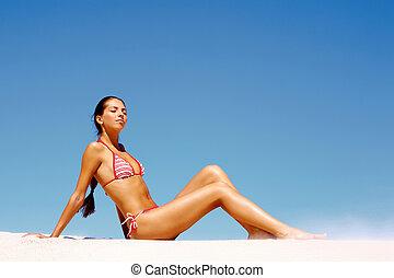 Sunbathing - Portrait of sunbathing girl sitting on the sand...