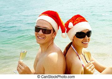 Sunbathing Santas - Portrait of attractive couple in Santa...