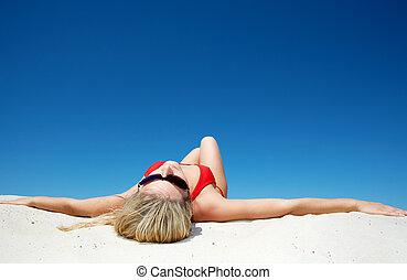 Sunbathing - View of beautiful woman sunbathing during...