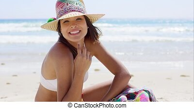 Sunbathing woman with white bikini smiles at camera while...