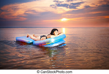 sunbathing - young girl lying down on the airbed
