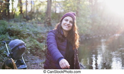 Sunbeam above beautiful woman smiling and making inviting gestures near a river in the forest. Happy woman smiling in forest with river as background. Adventurous day in nature
