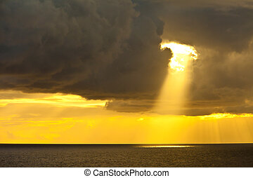 single sunbeam shining through dark clouds on the caribbean sea