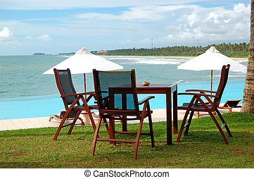 Sunbeds and chair of outdoor restaurant at the sea view swimming pool, Bentota, Sri Lanka