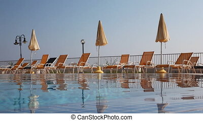 Sunbeds and umbrellas by pool with water
