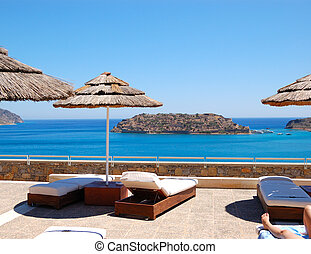 Sunbeds at luxury hotel with a view on Spinalonga Island, Crete, Greece