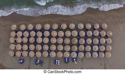 Sunbeds at the beach with few people relaxing there, aerial view