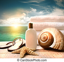 Sunblock lotion and towels and ocean scene - Sunblock lotion...