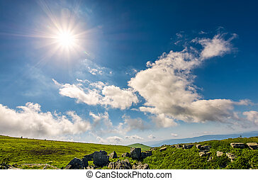 sunburst on a blue sky with clouds over the mountains with...
