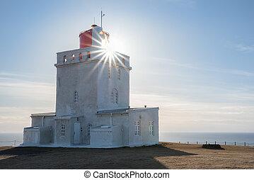 Sunburst shining through the Dyrholaey Lighthouse in Iceland