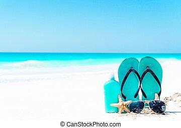 Suncream bottles, goggles, starfish and sunglasses on white sand beach background ocean
