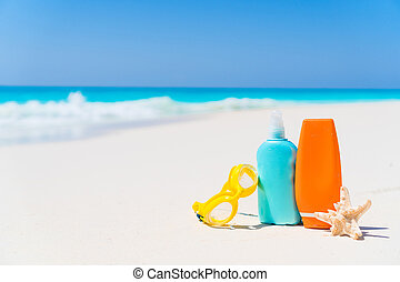 Suncream bottles, goggles, starfish on white sand beach background ocean