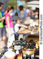 Market boot with objects beeing selled at the weekend flea market in the city center. Curious visitors in the background.
