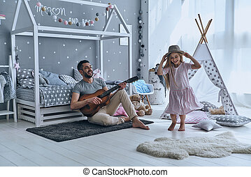 Sunday fun. Young father playing guitar for his little...