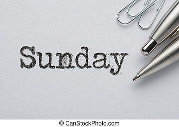 Sunday word printed with typewriter, pen and paper clips