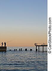 Sundown on sea. Three fisherman on pier