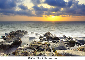 Sundown - Beautiful sundown at rocky beach. Water in motion...