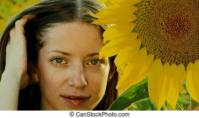 Sunflower - Close-up. The girl next to sunflowers.