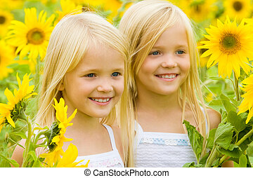 Sunflower happiness - Portrait of cute female twins looking...