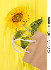 Sunflower in a bag lying on yellow wooden background.