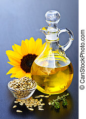 Sunflower oil bottle with raw seeds and flower