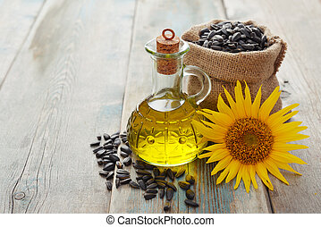 Sunflower oil in bottles with seeds and flower on wooden...