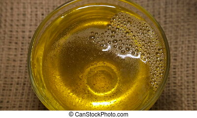 Sunflower seed oil in a glass bowl at the close-up rotation.