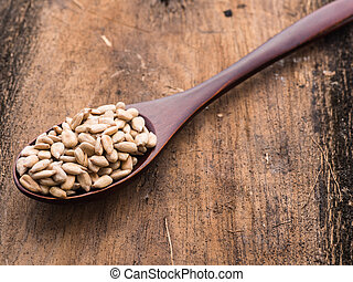 Sunflower seed on a wooden spoon with sunflower on wooden backgr