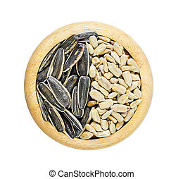 Sunflower seeds and shell in wooden dish.
