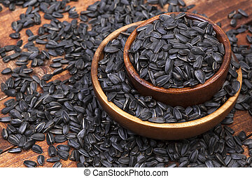 Sunflower seeds in bowl on dark wooden background