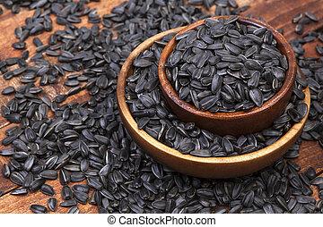 Sunflower seeds in bowl on dark wooden background