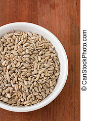 sunflower seeds in white bowl on brown background
