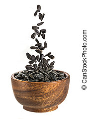 Sunflower seeds in wooden bowl isolated.