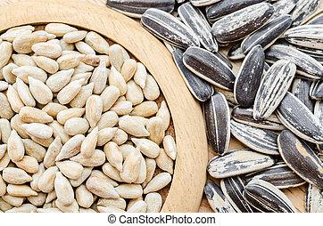 Sunflower seeds in wooden dish.