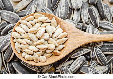 sunflower seeds in wooden spoon.