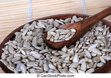 Sunflower seeds in a wood spoon, bowl.