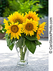 Sunflowers in a transparent glass vase on nature background...