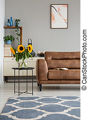 Sunflowers on table next to leather settee in apartment interior with poster and carpet. Real photo