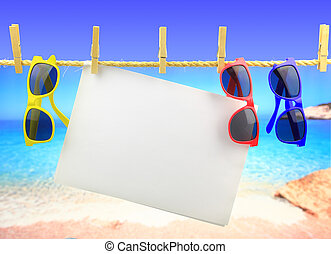 Sunglasses and banner hanging on a rope in front of the sea