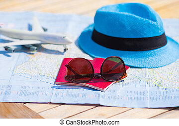 Sunglasses and passports, miniature airplane on the map. Travelling conception