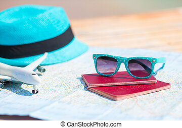 Sunglasses and passports, miniature airplane on the map. Travelling concept