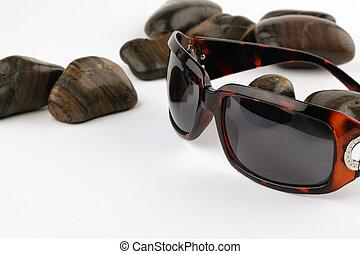 Sunglasses and pebbles - Stylish sunglasses and black ...