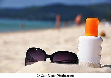 Sunglasses and sun lotion on the beach of Phuket island,...