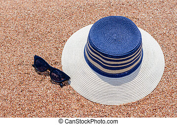Sunglasses and sunhat on a tropical beach