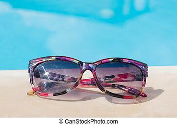 Sunglasses at the swimming pool. Summer vacation